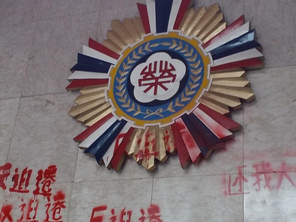 退輔會大廳的標誌被噴上「反迫遷」紅字。(攝影:張智琦)