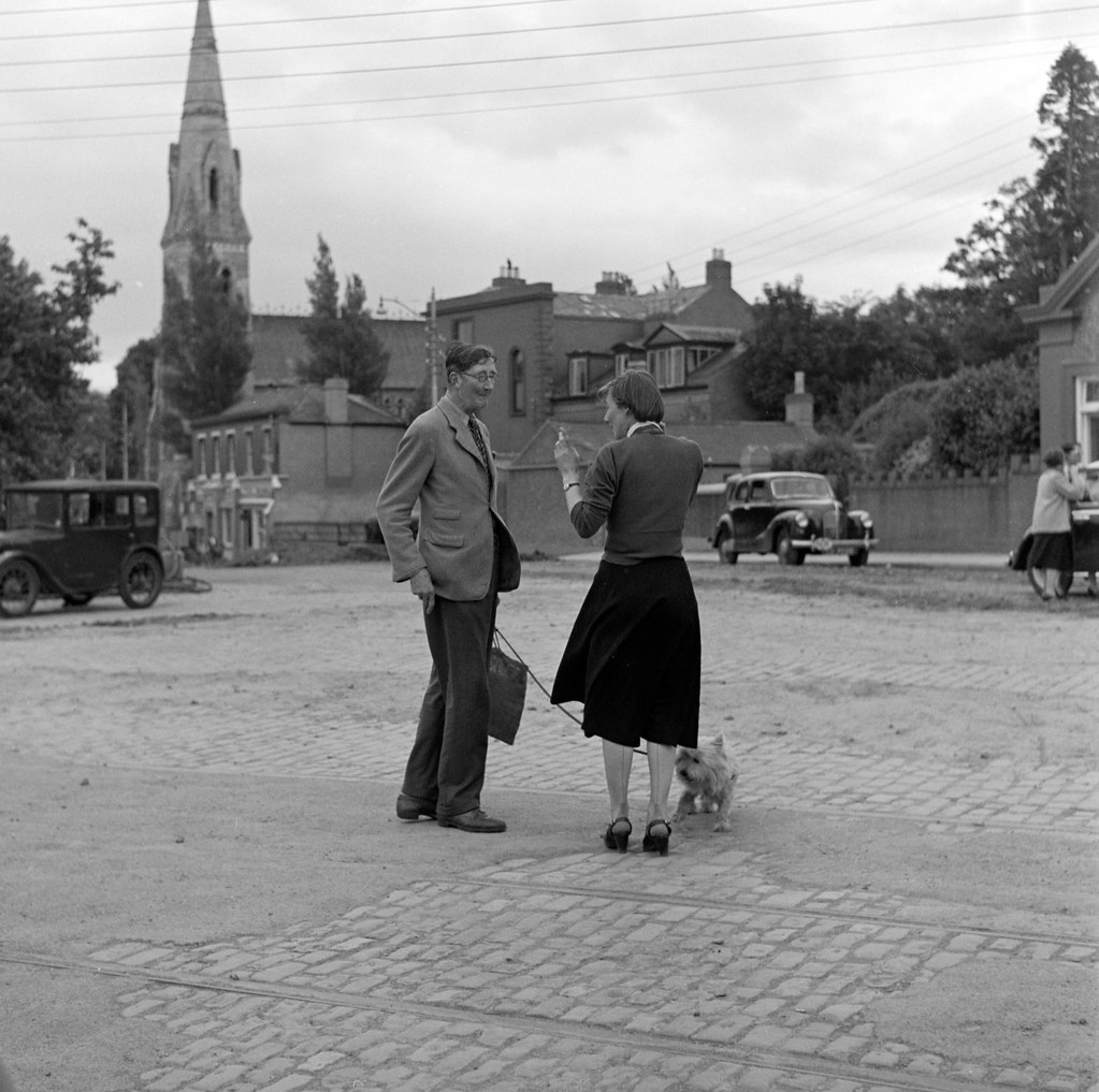 Man talking to woman in cobbled square, church visible in background, Co. Dublin | by National Library of Ireland on The Commons
