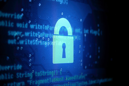 An image of a stylized lock in front of computer code