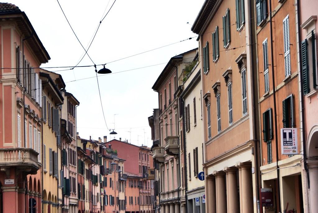 Une rue de Bologne avec deuex rangées de portiques et des façades multicolores.