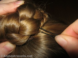 Put in the bobby pins to secure the braided bun - 12 Hiking Hairstyles that are Pretty & Practical