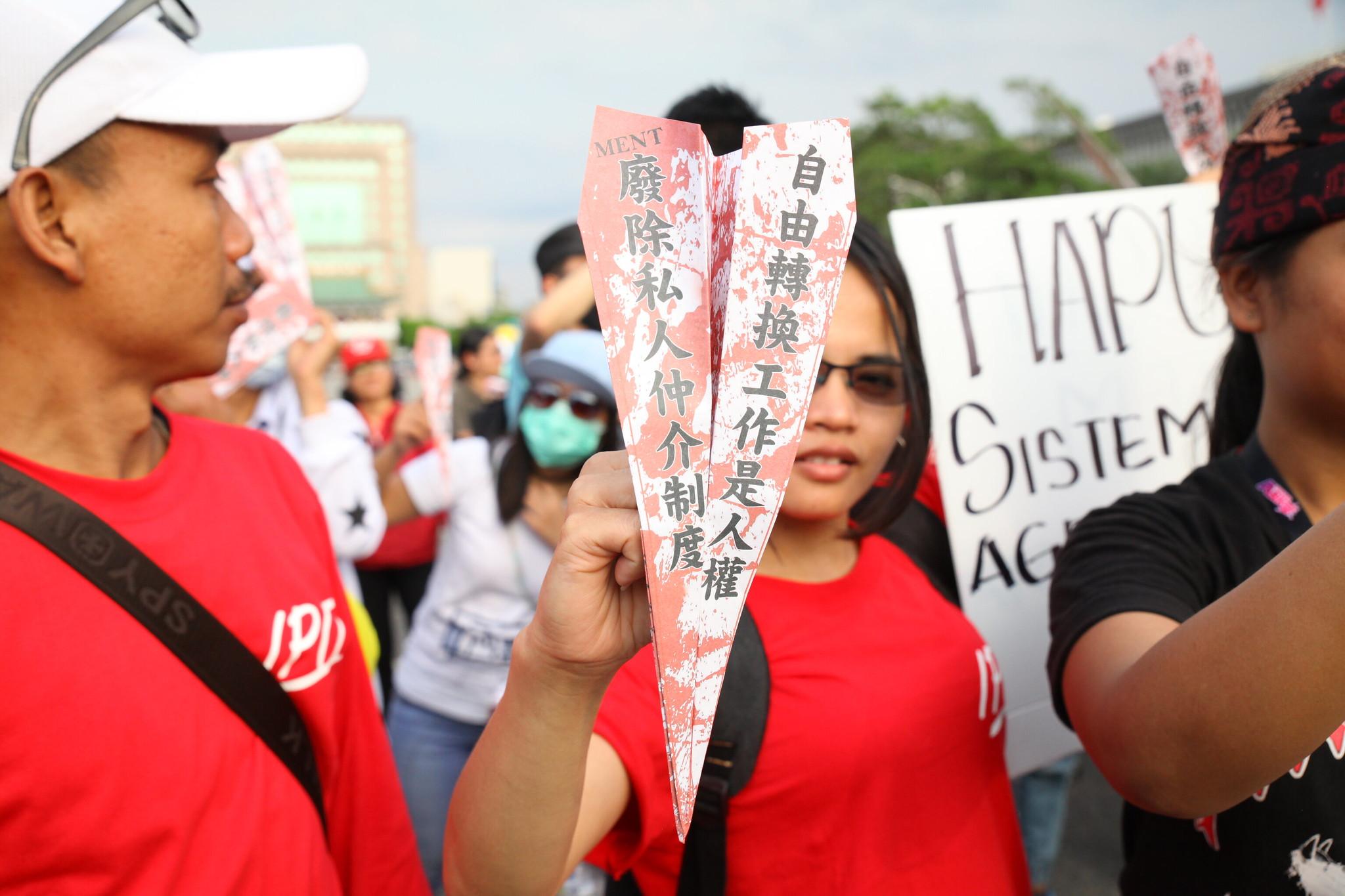 移工拿著寫有「自由轉換雇主訴求」的紙飛機,射向「結果呢」的蔡英文看板。(攝影:陳逸婷)
