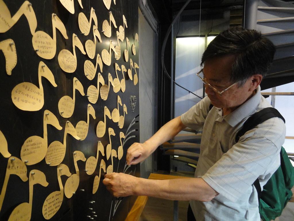 日本人田崎先生將留言的音符貼在金屬板上。(攝影:張智琦)
