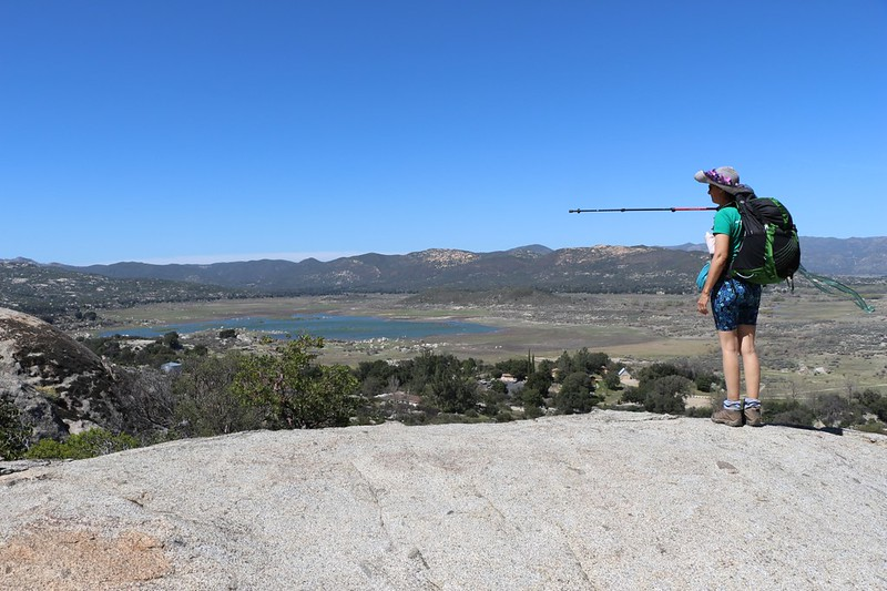 Vicki pointing toward Lake Morena from a granite slab on the PCT near mile 19