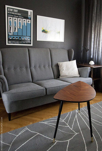 mid century modern living room with grey strandmon sofa wooden table and dark grey black wall with star trek poster  inspiration | by petiteapartment