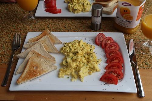 Frühstück mit Rührei, Toast und Tomate sowie Orangen-Mango-Saft