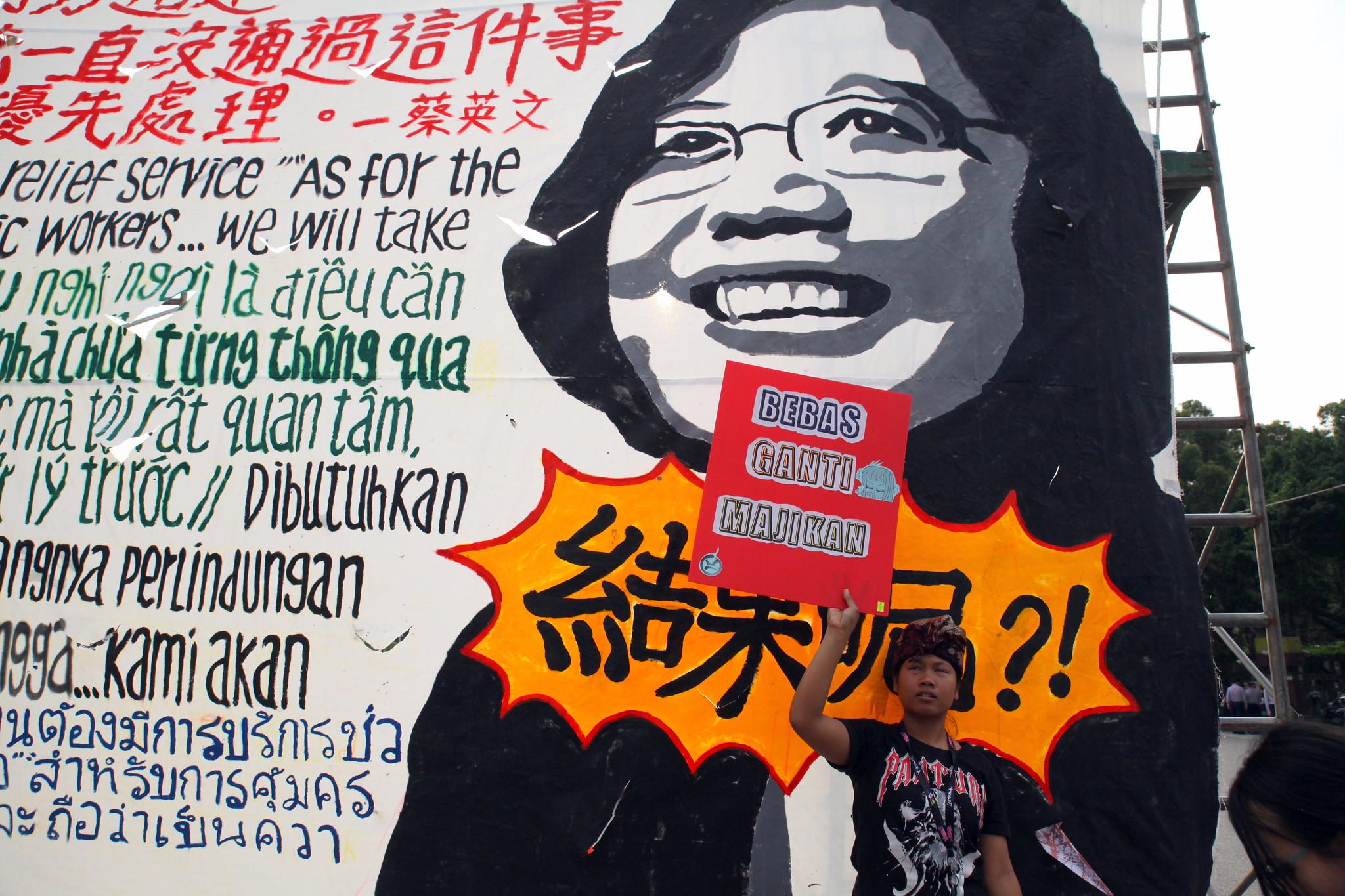 移工在蔡英文看板前舉牌「要轉換雇主」。(攝影:陳逸婷)
