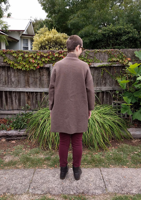 A woman stands against a garden fence. She wears maroon skinny jeans, brown boots and an oversized brown wool open coat.