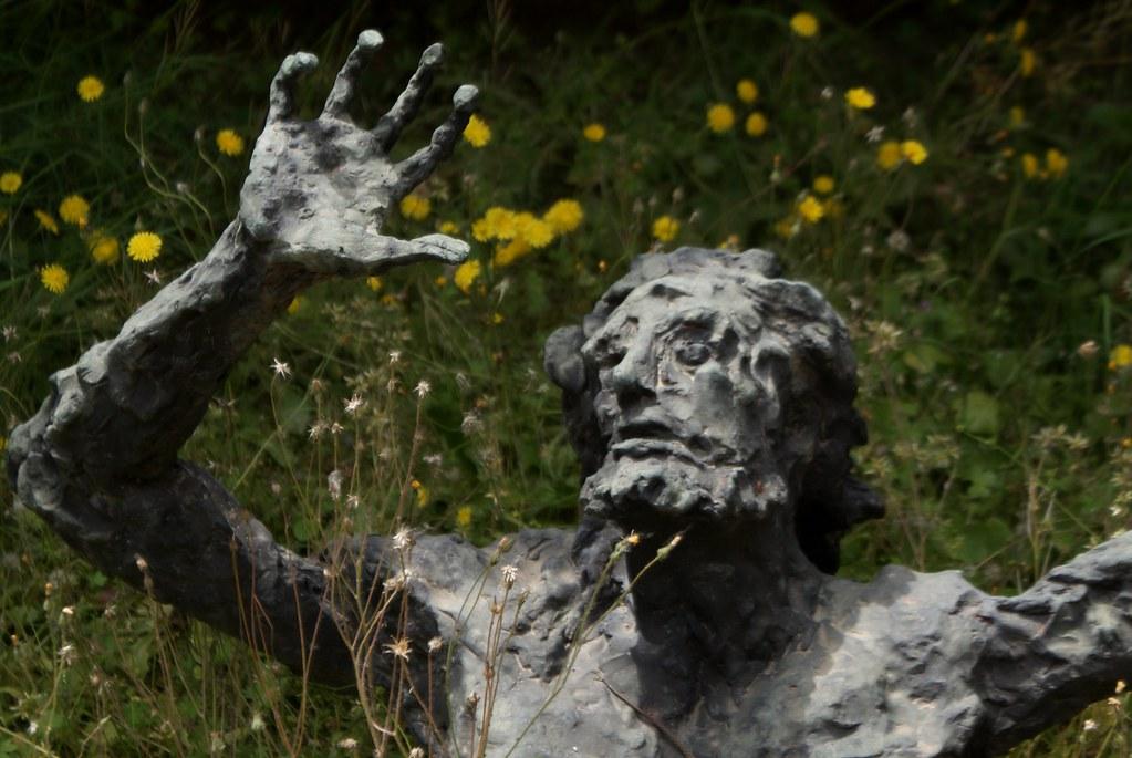 La statue sombre dans un lit de fleurs, oeuvre contemporaine du cimetière Certosa de Bologne.