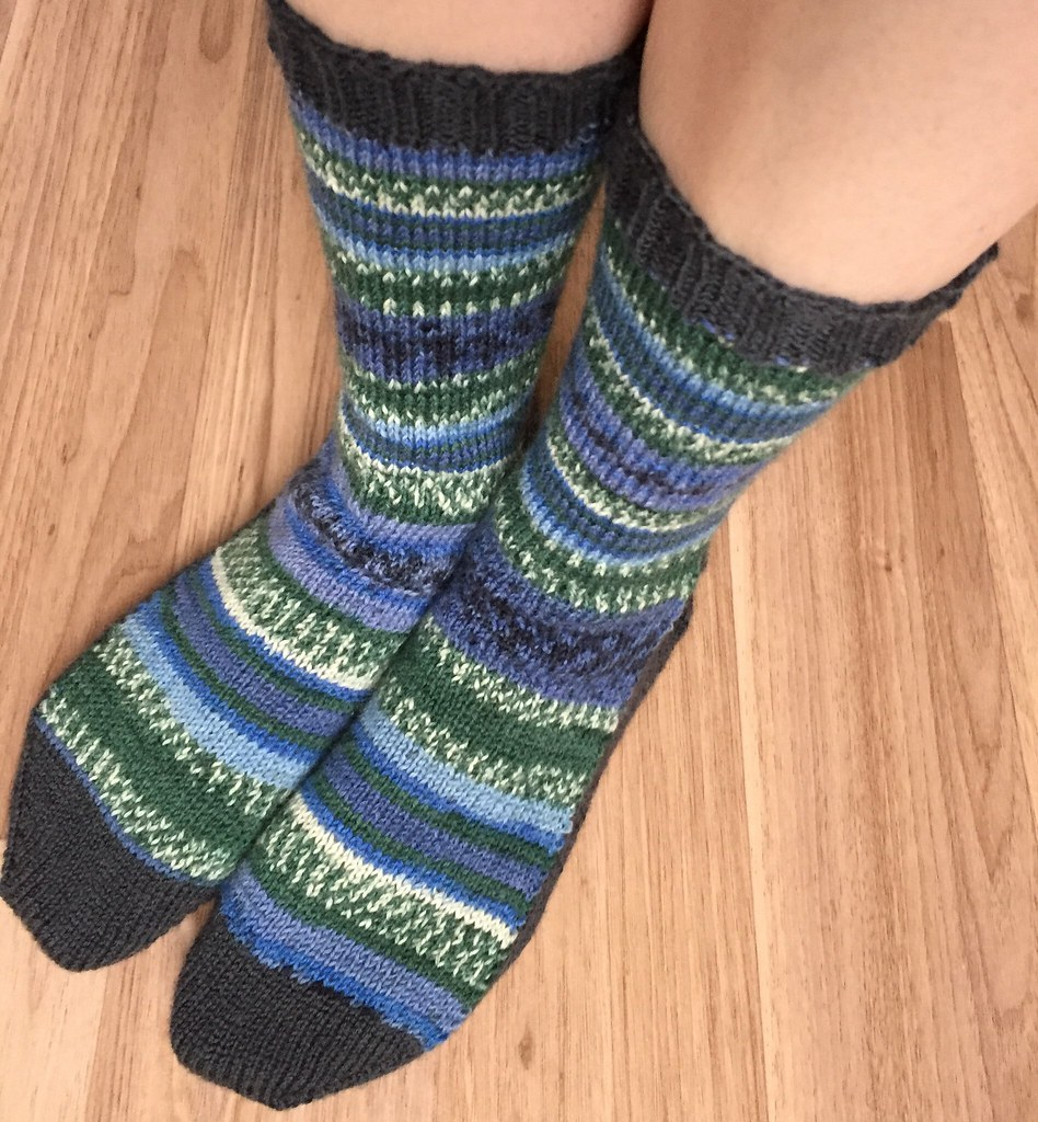 vanilla socks with the toe, sole, heel and ribbing knit in a slate grey yarn with the remaining portions knit in a self fair-isling yarn in blues and greens