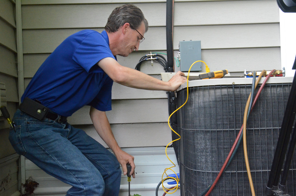 Man doing air conditioner maintenance as he looks forward to selling his house.