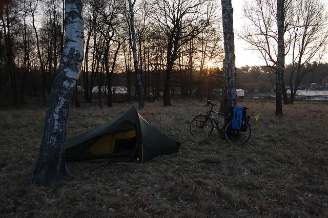 Bild: Sonnenaufgang, ein Fahrrad und das aufgebaute Zelt