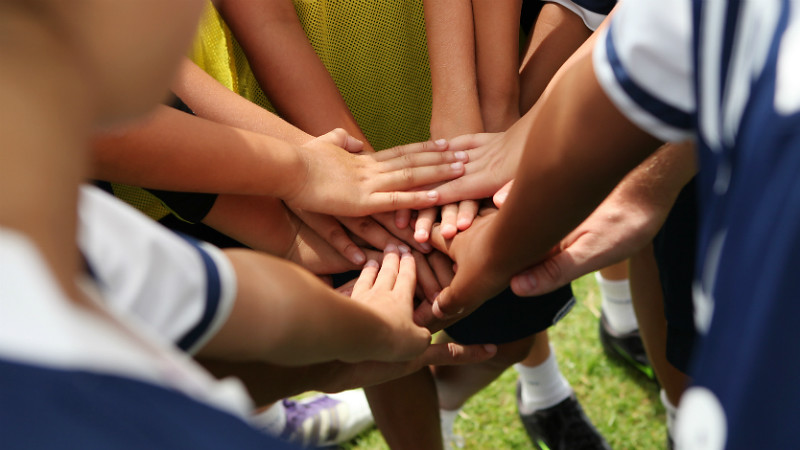 Children putting their hands together on a sports pitch