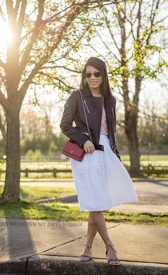 black leather jacket, pink lace top with bell sleeves, white clip dot midi skirt, stacked rings, red shoulder bag, suede sandals with jewels