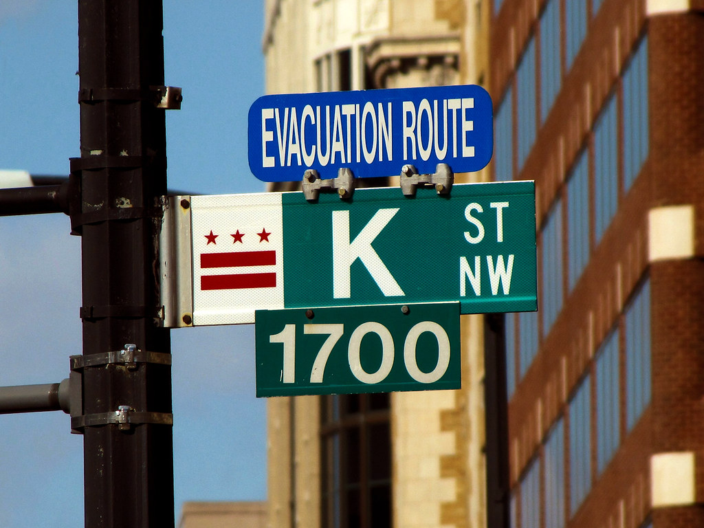 "K Street NW street sign with DC flag and ""EVACUATION ROUTE"" markings, at the northwest corner of Farragut Square."