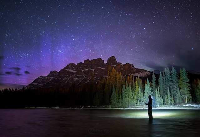 Aurora Angler... Self-portrait taken last night at Castle Mountain. The aurora storm was dying down but the camera revealed beautiful purples in the night sky. For me, part of the beauty of nighttime photography is how much the camera has the ability to s