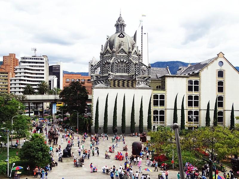 Parque com pessoas caminhando, árvores e o palácio da cultura em Medellín