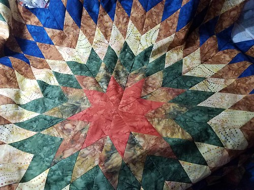 The center of the radiant star quilt is done and it looks amazing! It will have a blue background with swirls of rust and green in it.