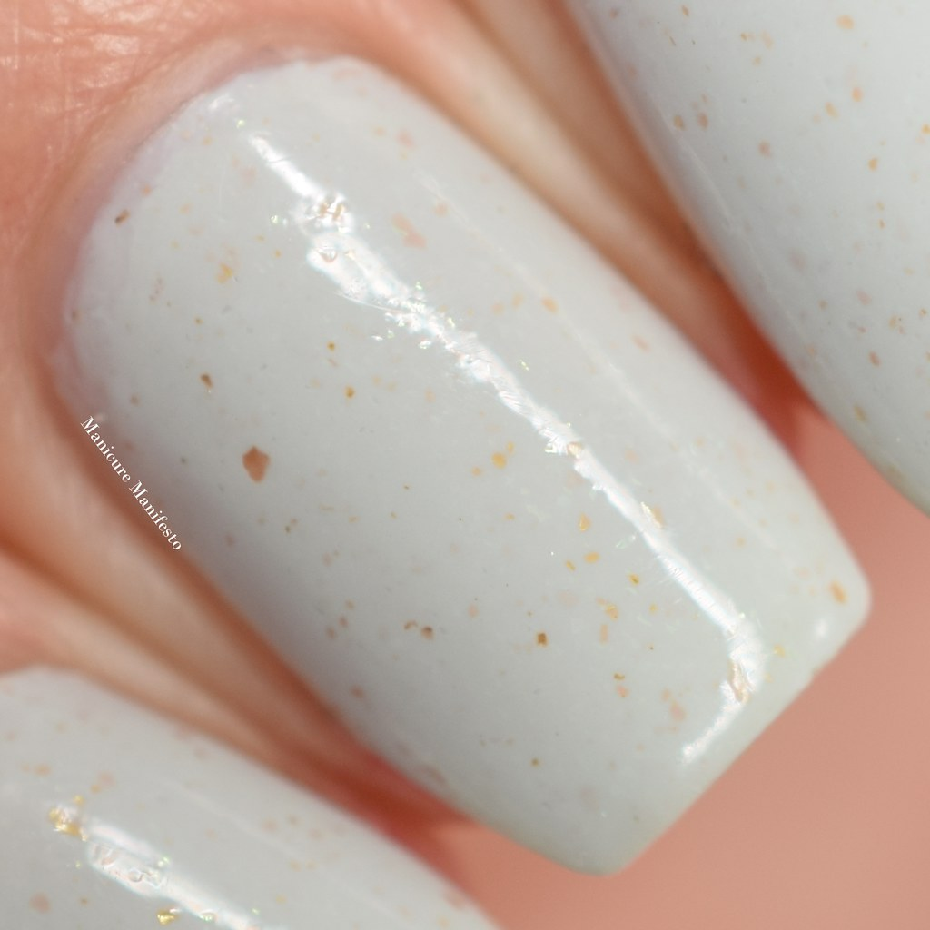 White with gold flakes nail polish