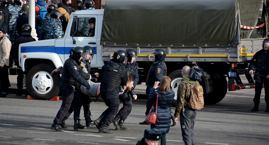 Четверо полицейских тащат в автозак
