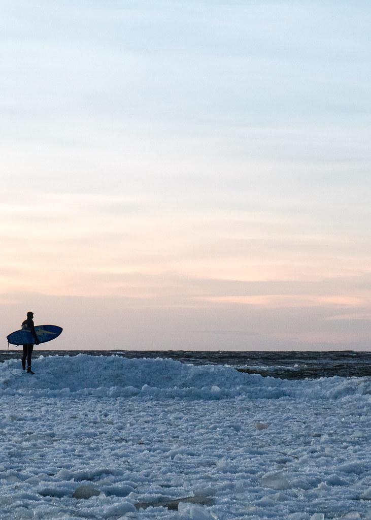 Surffaaja jäällä auringonlaskussa.