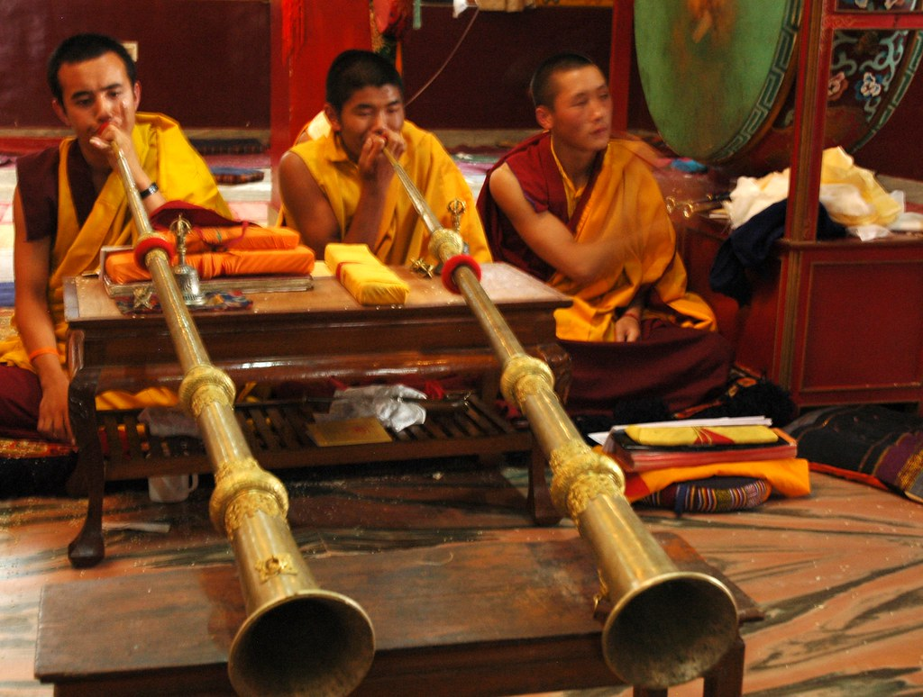 ... Tibetan Monks Playing Long Horns Propped Up On A Table, Beating The Big  Green Leather