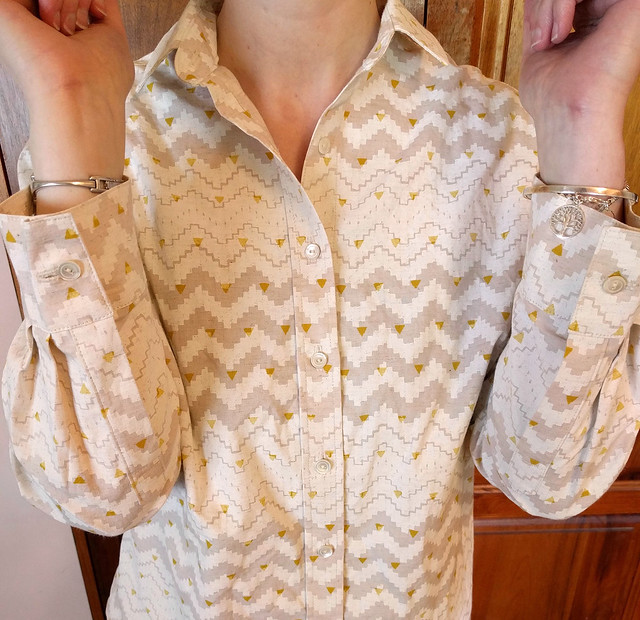 A woman wears a button up shirt. She bends her arms to show sleeve cuffs and plackets.