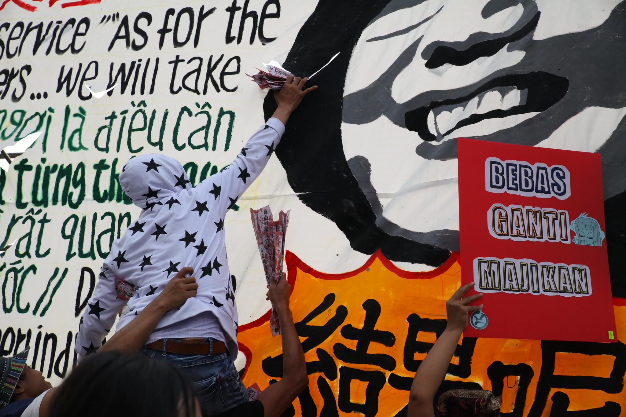 射飛機還不夠,移工把紙飛機直接塞在蔡英文看板上,表達憤怒。(攝影:陳逸婷)