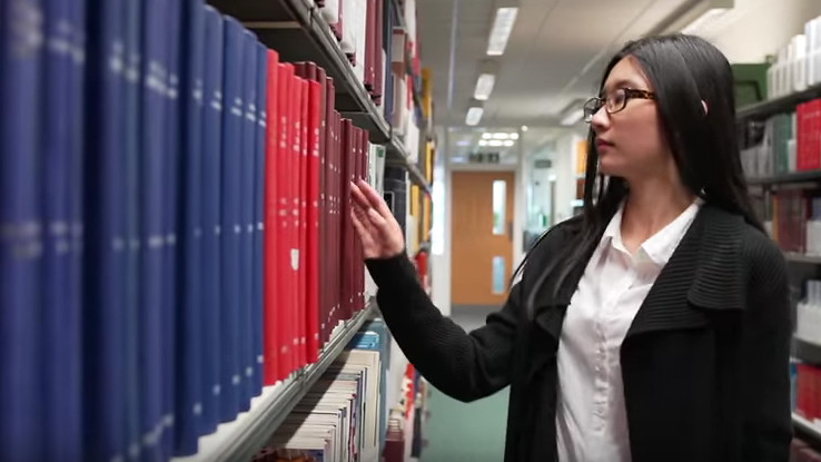 An MSc in Management student from China browses library books at the University of Bath
