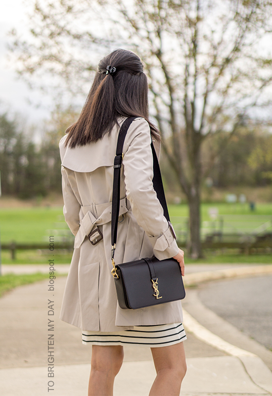 trench coat, striped dress with jeweled neckline, black shoulder bag