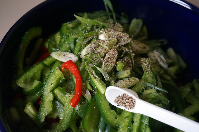 A pile of green pepper slices in a dark blue bowl, topped with a handful of green onion slices and dusted with black pepper. A single red pepper slice is visible atop the green -- it's rather striking.