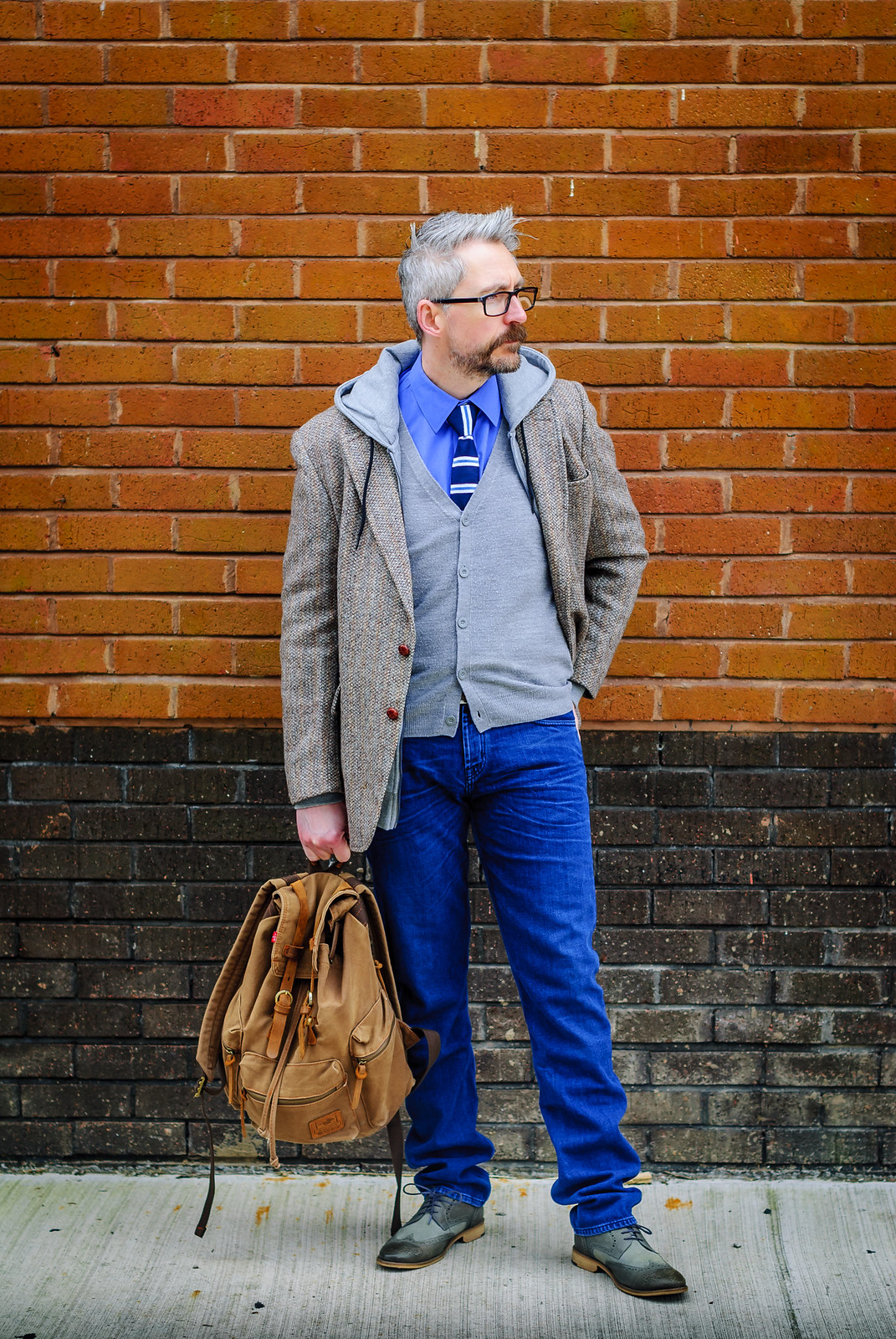 A layered smart casual outfit: Striped tie \ dress shirt \ grey cardigan \ grey hoodie \ Harris tweed jacket \ jeans \ grey brogues | Silver Londoner, over 40 menswear