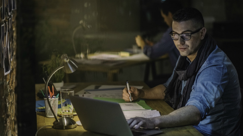 Man working on a laptop in a dimly lit office