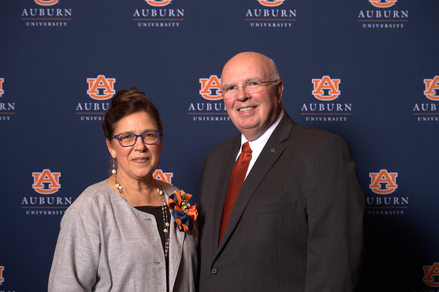 Barb Struempler and Timothy Boosinger pose for a photo in front of a navy blue Auburn University backdrop.