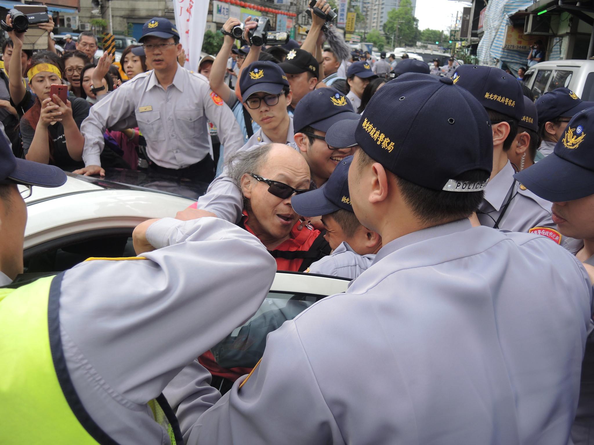 黎明幼兒園園長林金連遭警方強押上車。(攝影:曾福全)