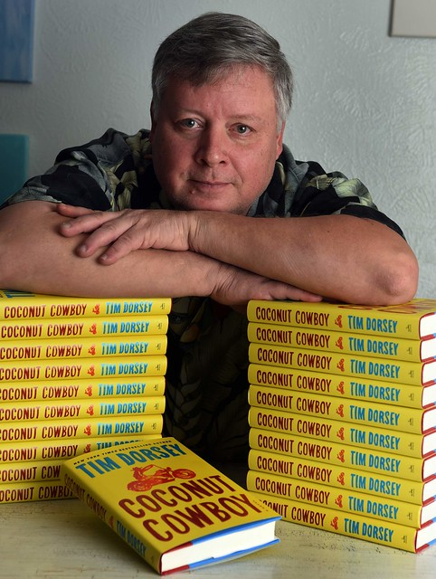 Photo of Tim Dorsey with several copies of his book.