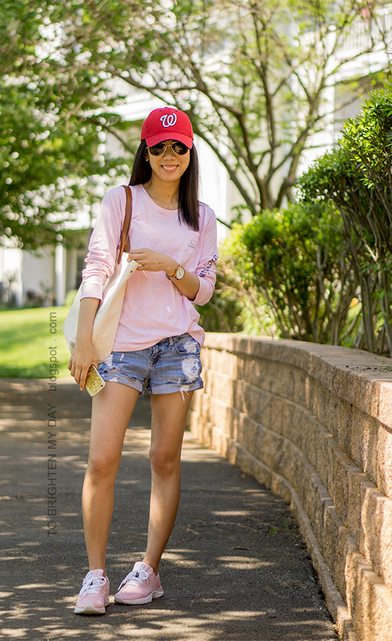 red baseball cap, pink graphic tee, oversized watch, canvas tote, distressed shorts, pink sneakers