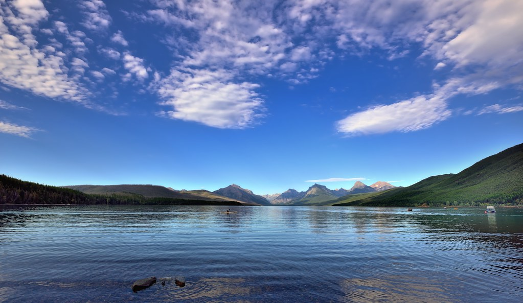 blue skies and clouds around lake mcdonald and mountains
