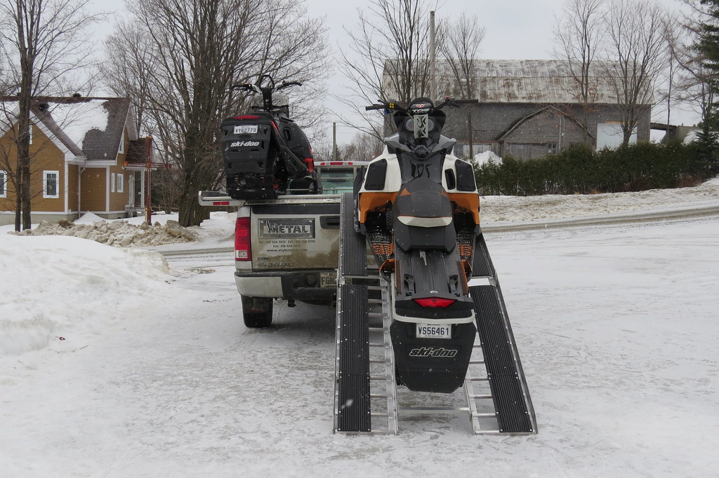 Snowmobiles Being Loaded Onto Modified Diamondback Truck B