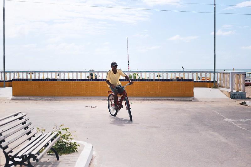 homem andando de bicicleta perto da praia