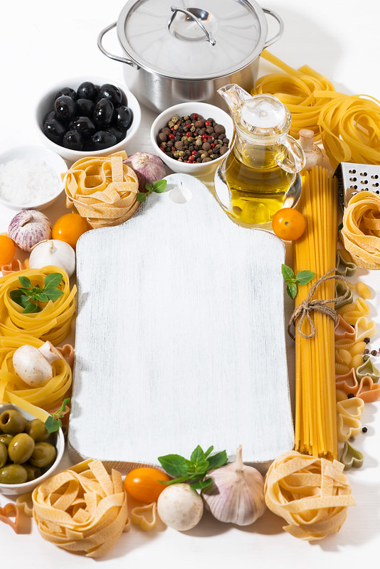 assortment of different pasta and wooden board for text, vertical