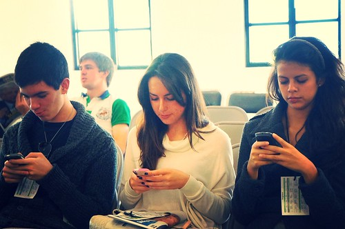 Three people sitting next to each other all looking at individual smartphones.