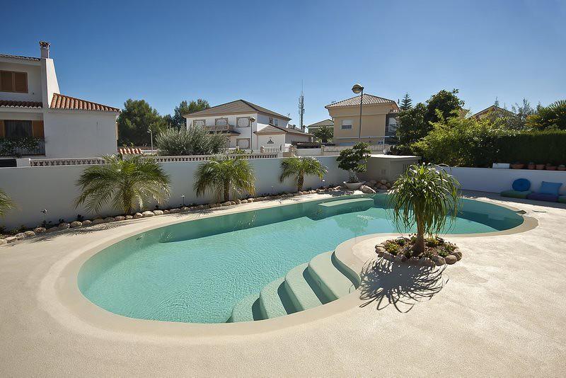 piscina de arena con agua de color turquesa y plantas sa