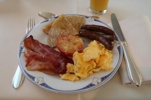 Pfannkuchen mit Ahornsirup, überbackene Tomate, Rührei, Würstchen und gebratener Speck
