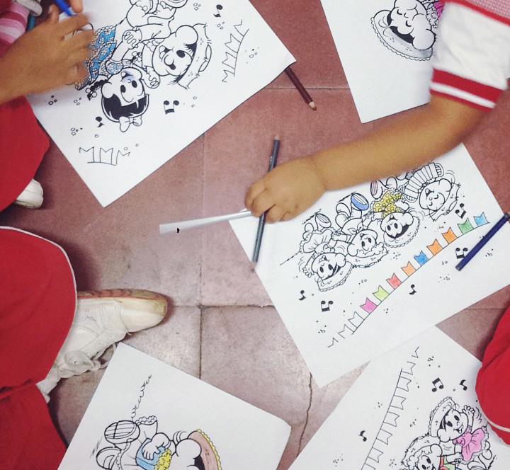 Crianças pintando desenhos da turma da mônica