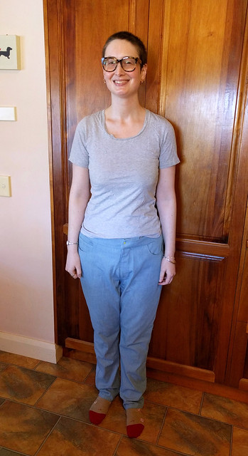 A woman wears baggy, unflattering jeans and a grey t-shirt.
