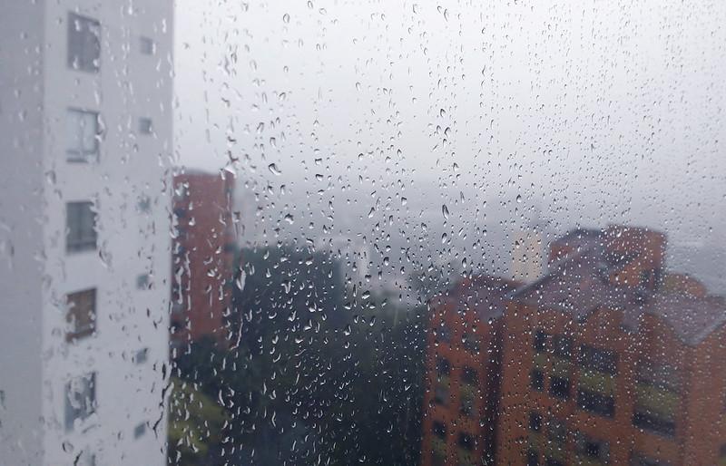 Janela com gotas de chuva e apartamentos no fundo