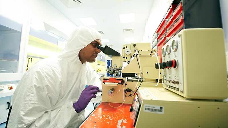 A researcher in a clean suit using laboratory equipment