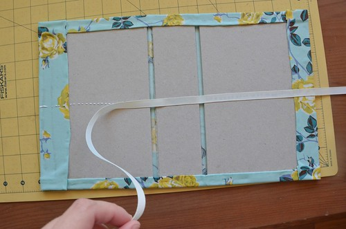 27. Center ribbon, and glue across book boards and cloth.