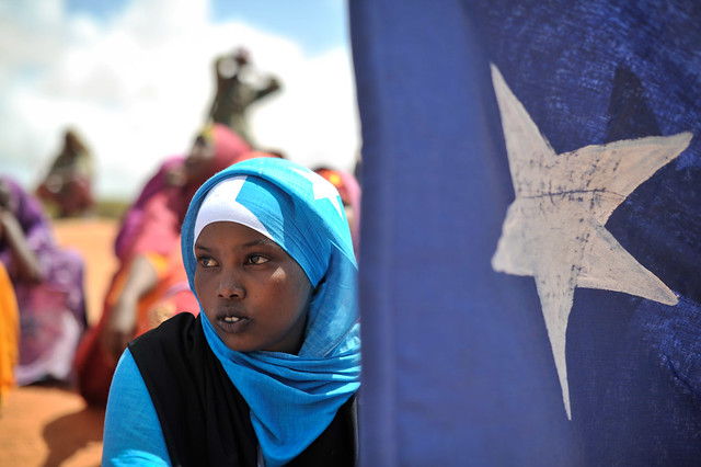 A young woman holds the Somali flag